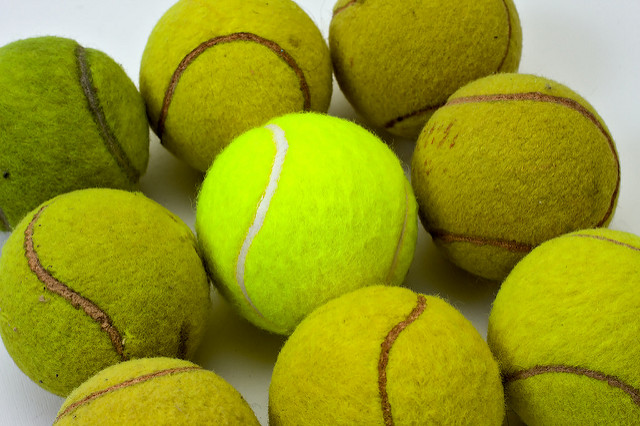 Brand new tennis ball with bright fluorescent green felt and white rubber band, surrounded by eight other used balls with duller, more washed out colors, deteriorated nap and dirt marks.